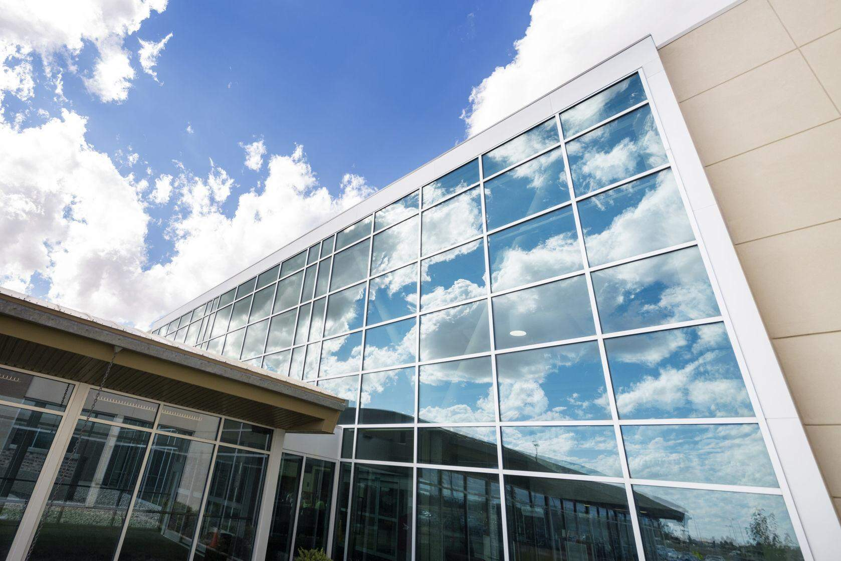 Low angle view of modern hospital building with reflection of clouds on glass windows